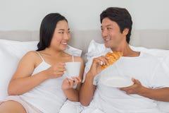 愉快的夫妇吃早餐在床 库存图片