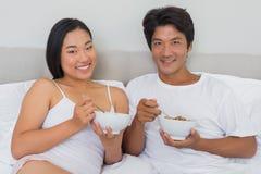 愉快的夫妇吃早餐在床 免版税库存照片