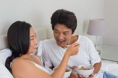 愉快的夫妇吃早餐在床 图库摄影