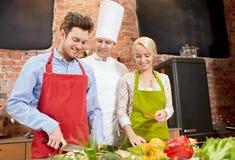 愉快的夫妇和男性厨师在厨房里烹调烹调 免版税库存图片