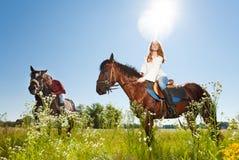 愉快的夫妇和他们的公马在用花装饰的草甸 图库摄影
