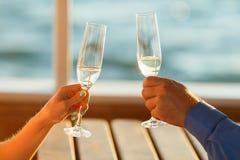愉快的夫妇喝在游艇的香槟 免版税库存照片