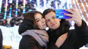 愉快的夫妇在一个现代电话做一selfie,微笑和亲吻在新年的夜 股票录像