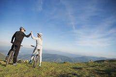 愉快的夫妇在一条山柏油路去在自行车的森林有给高五的盔甲的 图库摄影