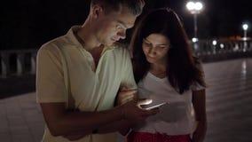 愉快的夫妇在一起观看在智能手机的街道上的晚上 股票录像