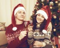 愉快的夫妇在与杯的圣诞树附近坐香槟 寒假和爱概念 被定调子的黄色 图库摄影