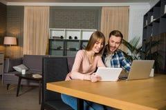 愉快的夫妇在与膝上型计算机和数字式片剂的桌上在客厅 免版税库存图片