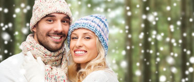 愉快的夫妇在冬天佩带在森林和雪 免版税库存图片