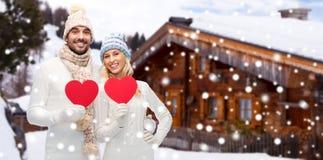 愉快的夫妇在冬天穿衣与心脏户外 免版税库存照片