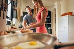 愉快的夫妇在厨房里 免版税库存图片