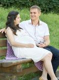 愉快的夫妇在夏天城市停放室外,孕妇、明亮的晴天和绿草,美丽的人画象,黄色口气 免版税图库摄影
