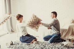 愉快的夫妇在客厅开玩笑地举行在沙发的枕头战 库存照片