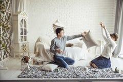 愉快的夫妇在客厅开玩笑地举行在沙发的枕头战 免版税库存图片