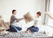 愉快的夫妇在客厅开玩笑地举行在沙发的枕头战 免版税库存照片