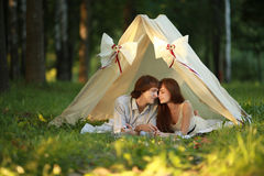 愉快的夫妇在帐篷亲吻夏天晚上 免版税库存图片