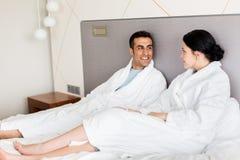 愉快的夫妇在床在家或旅馆客房上 免版税库存图片