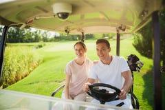 愉快的夫妇在打高尔夫球的一辆白色高尔夫车乘坐 妇女在人` s肩膀放置了她的手 免版税图库摄影