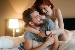 愉快的夫妇在显示情感的床上 免版税图库摄影