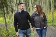 年轻愉快的夫妇在森林草甸 免版税库存照片