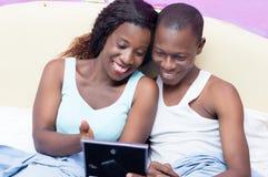 愉快的夫妇在看照片的床上 免版税库存照片