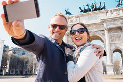 愉快的夫妇在米兰拍在和平曲拱的一张selfie照片  库存照片