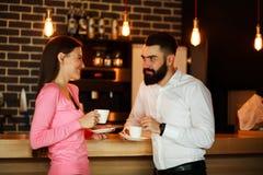 年轻愉快的夫妇在酒吧和谈话见面了与咖啡 库存图片