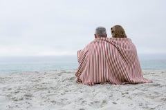 愉快的夫妇坐与毯子的沙子在他们附近 免版税库存照片