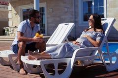 愉快的夫妇坐在房子前面的躺椅有poo的 免版税库存照片
