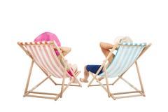 愉快的夫妇坐海滩睡椅 库存照片