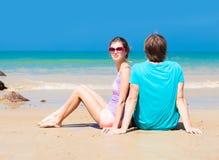 年轻愉快的夫妇坐热带海滩  库存图片