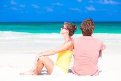 年轻愉快的夫妇坐热带海滩 免版税库存图片