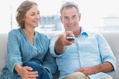 愉快的夫妇坐看电视的长沙发 库存照片