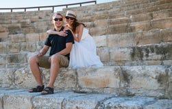 愉快的夫妇坐老石步 免版税图库摄影