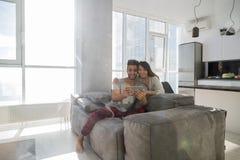 愉快的夫妇坐长沙发使用与全景窗口的片剂计算机现代公寓 免版税图库摄影