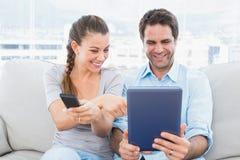 愉快的夫妇坐长沙发使用片剂个人计算机和观看的电视 库存照片