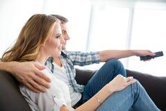 愉快的夫妇坐长沙发和观看的电视 免版税库存照片