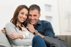 愉快的夫妇坐长沙发 图库摄影