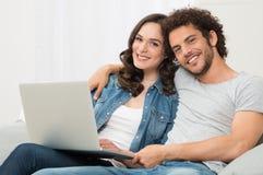 愉快的夫妇坐长沙发 免版税图库摄影
