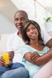 愉快的夫妇坐饮用的长沙发汁液 免版税库存图片