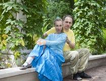 年轻愉快的夫妇坐以树荫处被缠绕的绿色 库存照片