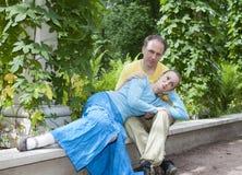 年轻愉快的夫妇坐以树荫处被缠绕的绿色 库存图片