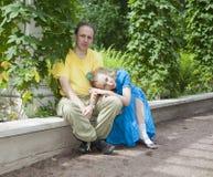 年轻愉快的夫妇坐以树荫处被缠绕的绿色 免版税库存照片