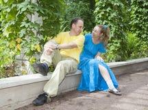 年轻愉快的夫妇坐以树荫处被缠绕的绿色 免版税库存图片