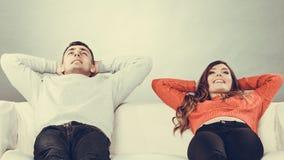 愉快的夫妇放松的在家基于长沙发 免版税库存照片