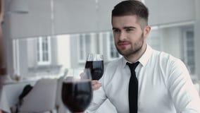 年轻愉快的夫妇浪漫日期饮料杯在餐馆的红葡萄酒,庆祝情人节 库存图片