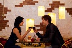 年轻愉快的夫妇浪漫日期饮料玻璃  免版税库存照片