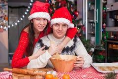 年轻愉快的夫妇烘烤圣诞节画象  库存照片