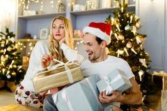 愉快的夫妇照片在圣诞老人盖帽的有在箱子的礼物的 免版税库存照片