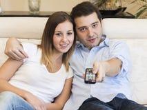 愉快的夫妇电视家 免版税库存图片