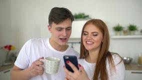 愉快的夫妇男人和妇女在家在早餐的厨房里使用一起浏览的智能手机在网上有乐趣喝 股票视频